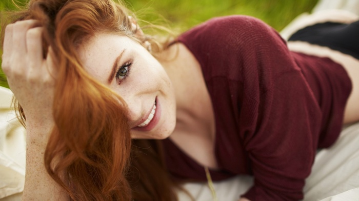 girl outdoors, lying down, looking at viewer, depth of field, freckles, smiling, face, girl, long hair, redhead, model