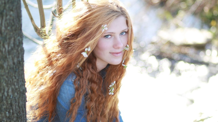 flower in hair, blue eyes, curly hair, redhead, girl outdoors, looking at viewer, sunlight, girl, model, face, jacket, nature, long hair, trees, smiling