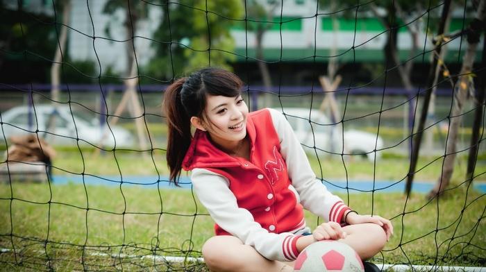 Goal, sitting, model, smiling, girl outdoors, long hair, brunette, soccer ball, sports, grass, trees, holding knees, ponytail, girl, soccer pitches, sports jerseys, Asian, nets