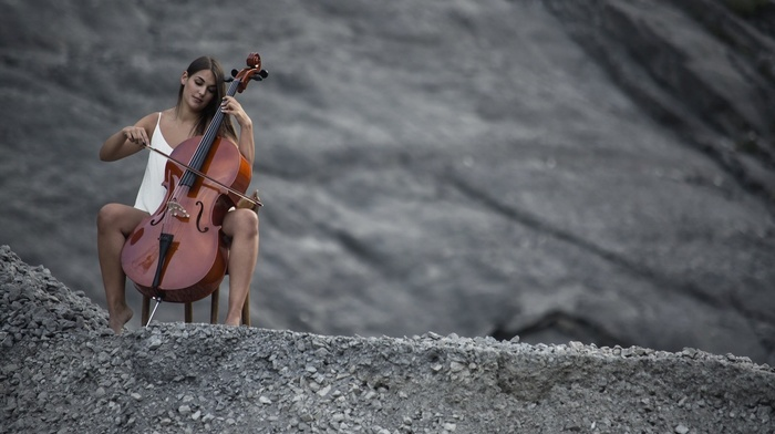 white clothing, playing, brunette, looking down, girl outdoors, contrabass, chair, spread legs, long hair, hill, girl, sitting, model, nature, music, stones, barefoot