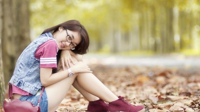 girl outdoors, long hair, denim skirt, girl with glasses, short skirt, sitting, looking at viewer, glasses, T, shirt, nature, jeans, girl, smiling, trees, fall, model, brunette, Asian, forest, leaves