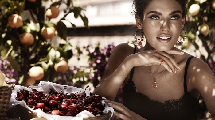 orange fruit, Bianca Balti, table, brunette, shadow, sitting, open mouth, model, girl outdoors, cherries, long hair, baskets, looking away, earrings, hand, black clothing, bare shoulders, fruit, trees, girl