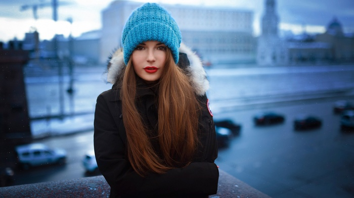 city, lipstick, depth of field, looking at viewer, winter, girl outdoors, girl, auburn hair, snow, hat, woolly hat, long hair, smooth skin, brunette
