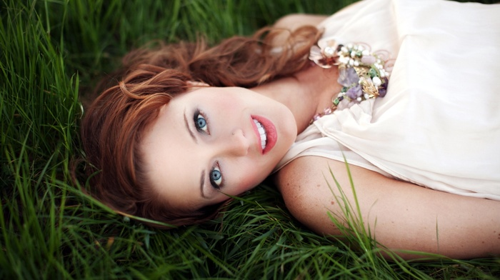 girl outdoors, grass, lying on back, open mouth, model, long hair, girl, looking at viewer, necklace, pierced nose, depth of field, smiling, redhead, blue eyes, white clothing, face