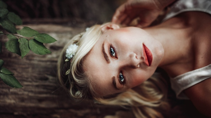 red lipstick, flower in hair, tank top, girl, leaves, long hair, looking at viewer, face, wood, model, blue eyes, nature, trees, blonde, girl outdoors, depth of field, white tops, portrait, bare shoulders