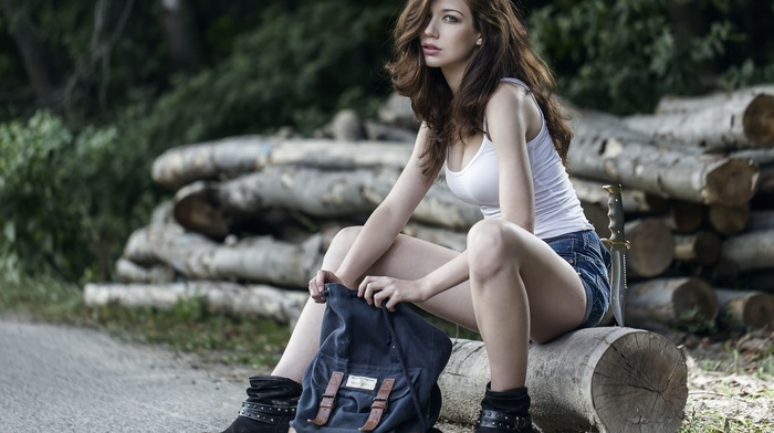 hair in face, black boots, sitting, road, bare shoulders, girl, jeans, legs, trees, tank top, knife, long hair, brunette, girl outdoors, backpacks, wood, jean shorts, model, open mouth, looking at viewer, nature