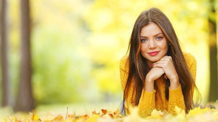looking at viewer, sweater, smiling, long hair, face, girl outdoors, trees, red lipstick, depth of field, portrait, fall, model, nature, girl, blue eyes, brunette, lying on front, leaves