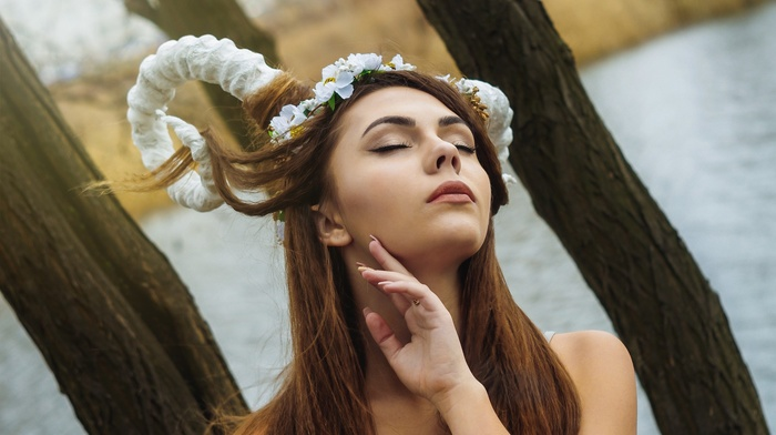 face, long hair, trees, branch, model, wavy hair, brunette, girl, portrait, girl outdoors, water, closed eyes, flower in hair, horns, depth of field, makeup, nature, bare shoulders, hand