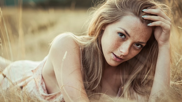 hands in hair, girl, face, looking at viewer, nature, brown eyes, girl outdoors, long hair, bare shoulders, lying on front, grass, field, freckles, model, Olga Kobzar, depth of field