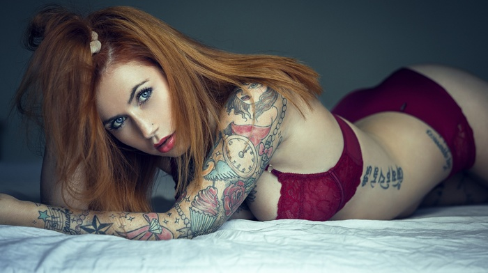 in bed, lingerie, red lipstick, arched back, hands in hair, blue eyes, cleavage, pierced nose, girl, ass, tattoo, long hair, lying on front, looking at viewer, panties, redhead, model