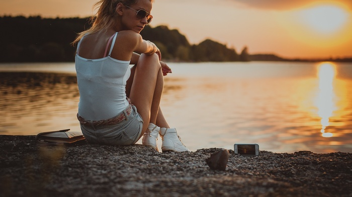 sunset, iPhone, girl outdoors, glasses, blonde, depth of field, girl, riverside, tanned, jean shorts, long hair, sitting, rear view, ponytail