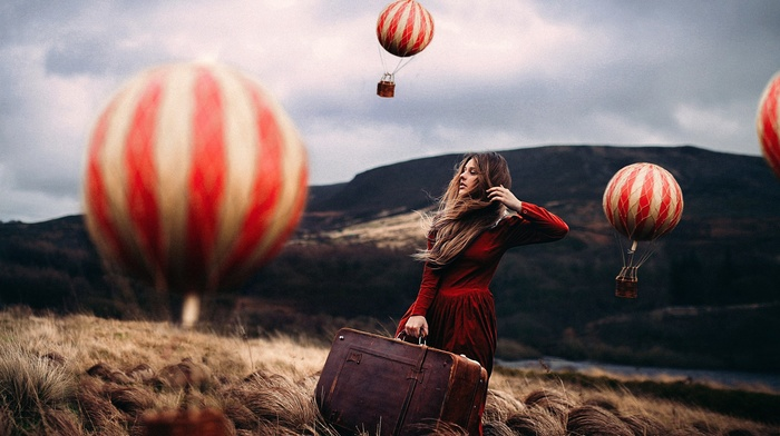 windy, blonde, hot air balloons, looking away, grass, model, miniatures, depth of field, red dress, nature, field, long hair, hills, suitcase, girl outdoors, fantasy art, girl, photo manipulation, clouds