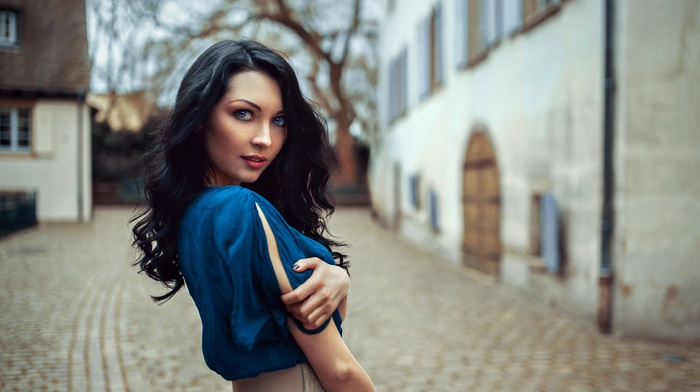 depth of field, looking at viewer, dress, model, face, long hair, girl, blue eyes, blue dress, dark hair, curly hair, girl outdoors
