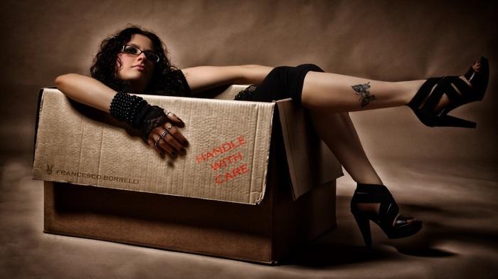 girl with glasses, girl, wavy hair, black heels, legs, brunette, model, looking at viewer, rings, gloves, black clothing, legs up, tattoo, cardboard, long hair, glasses, high heels