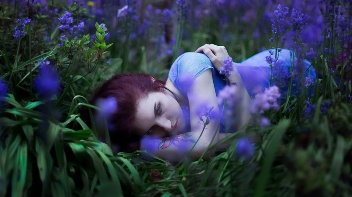 model, blue dress, redhead, depth of field, girl, field, grass, girl outdoors, flowers, lying on side, nature, looking away, long hair, tattoo