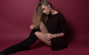 black stockings, blonde, girl, sitting, looking down, simple background
